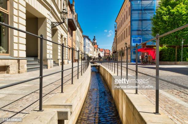 canal amidst buildings against sky in city - lutherstadt wittenberg stock pictures, royalty-free photos & images