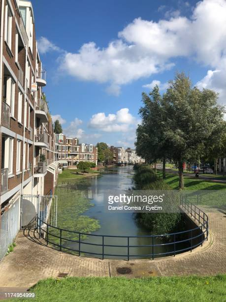 canal amidst buildings against sky in city - dordrecht stock pictures, royalty-free photos & images