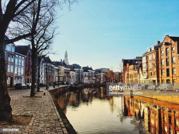 canal amidst buildings against sky in city - groningen province stock photos and pictures