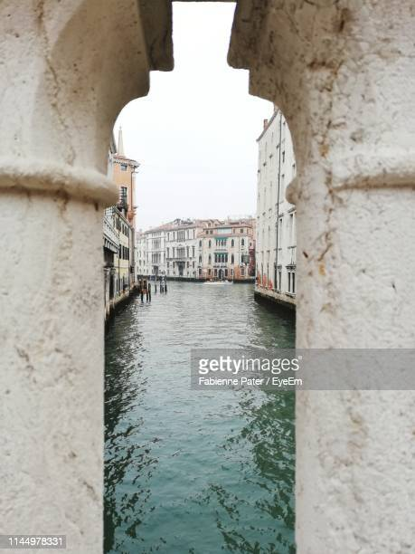 canal amidst buildings against sky - canale foto e immagini stock