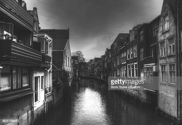 canal amidst buildings against sky - dordrecht stock pictures, royalty-free photos & images