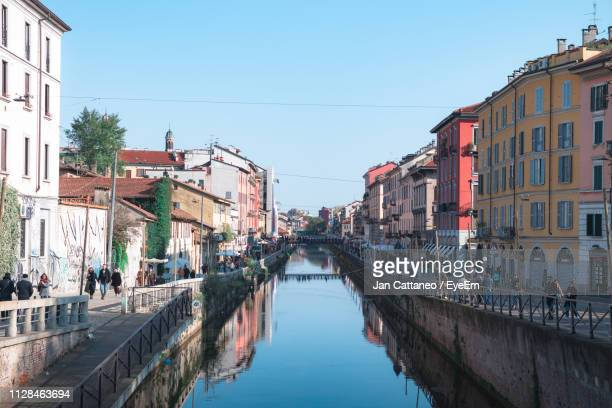 canal amidst buildings in city against clear sky - lombardia foto e immagini stock