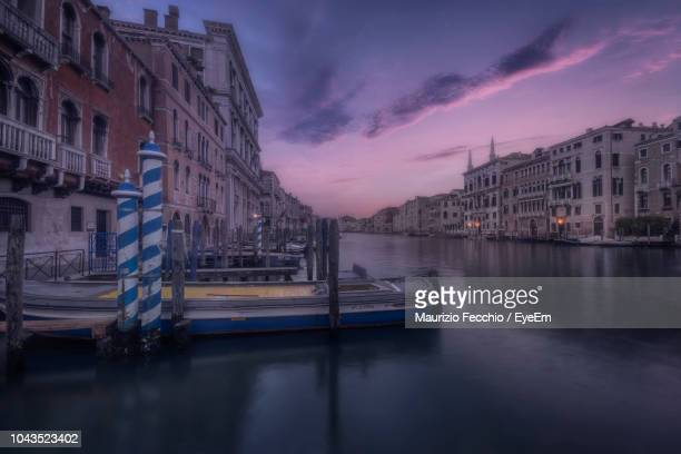 canal amidst buildings in city against sky at sunset - maurizio fecchio foto e immagini stock