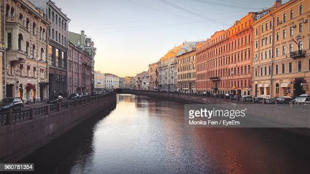 canal amidst buildings in city against sky at sunset - サンクトペテルブルク ストックフォトと画像
