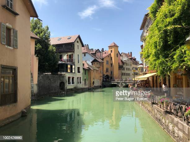canal amidst buildings in city against sky - フランス アヌシー ストックフォトと画像
