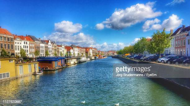 canal amidst buildings in city against sky - zeeland stock pictures, royalty-free photos & images