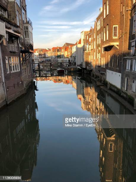 canal amidst buildings in city against sky - dordrecht stock pictures, royalty-free photos & images