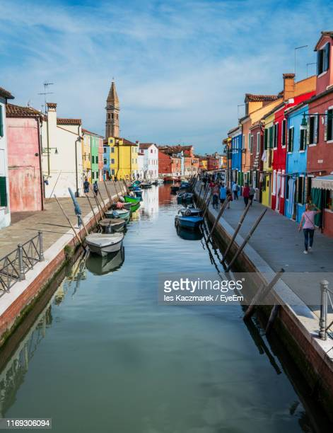 canal amidst buildings in city against sky - burano foto e immagini stock