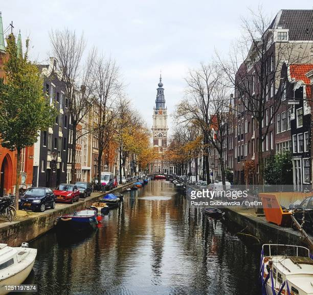canal amidst buildings in city against sky - north holland stock pictures, royalty-free photos & images