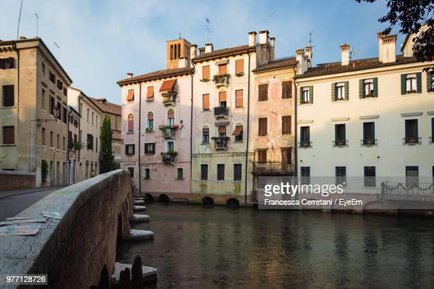canal amidst buildings in city against sky - treviso italy stock pictures, royalty-free photos & images