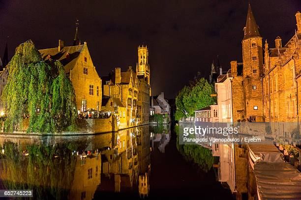 canal amidst buildings in city at night - vgenopoulos stock pictures, royalty-free photos & images
