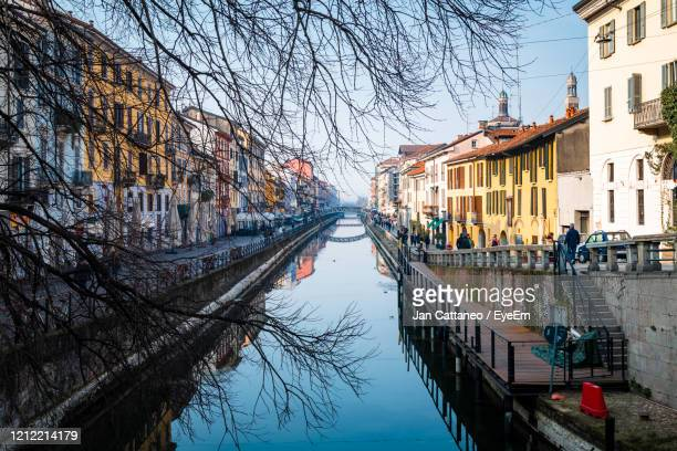 canal amidst buildings in city during winter - milan stock pictures, royalty-free photos & images