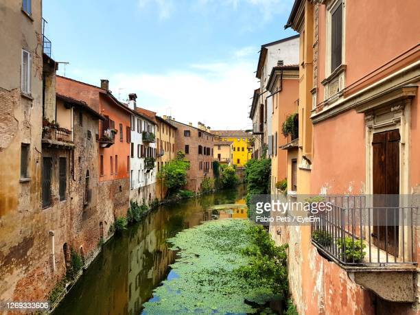 canal amidst buildings in mantova - mantua stock pictures, royalty-free photos & images