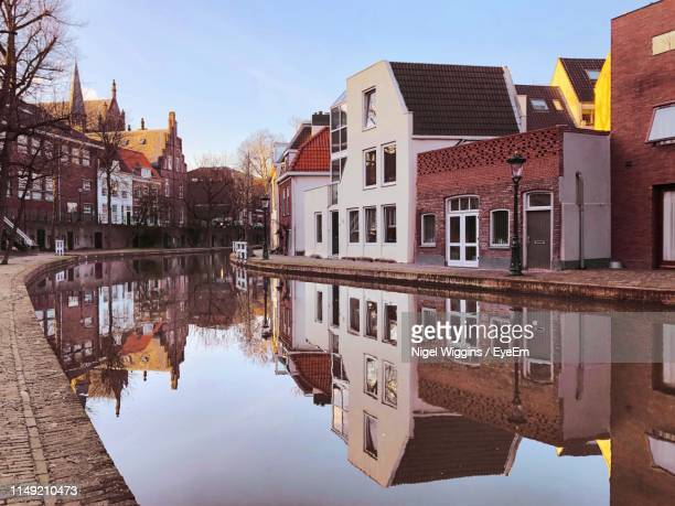 canal amidst buildings in town against sky - utrecht stock-fotos und bilder