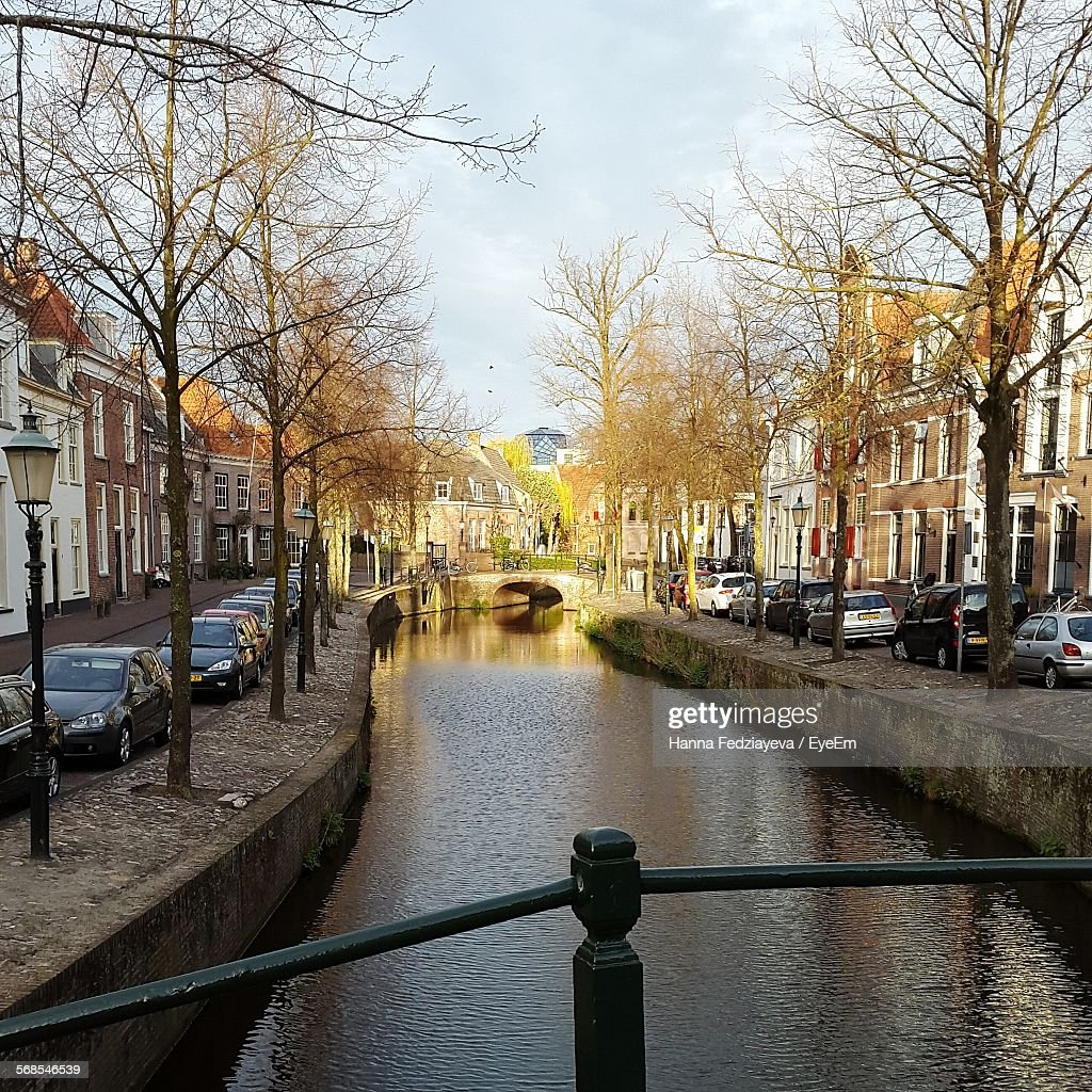 Canal Amidst Cars Parked By Houses : Stock Photo