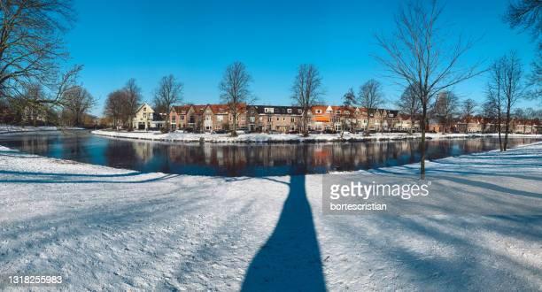 canal amidst frozen trees against sky during winter - bortes stockfoto's en -beelden