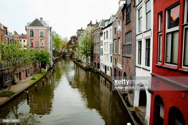 canal amidst houses against clear sky - utrecht stock pictures, royalty-free photos & images