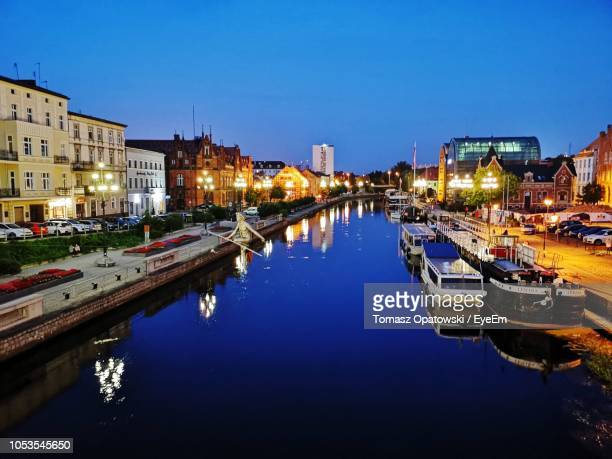 canal amidst illuminated buildings in city at night - bydgoszcz stock pictures, royalty-free photos & images