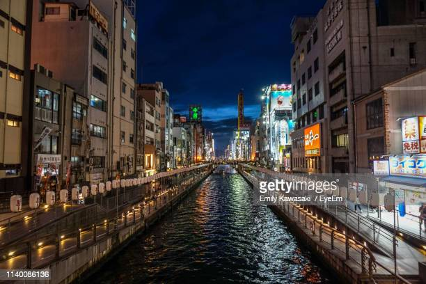 canal amidst illuminated buildings in city at night - 運河 ストックフォトと画像