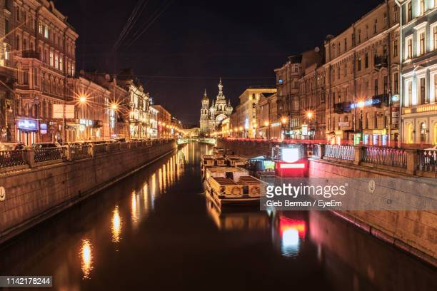 canal amidst illuminated buildings in city at night - st. petersburg russia stock pictures, royalty-free photos & images