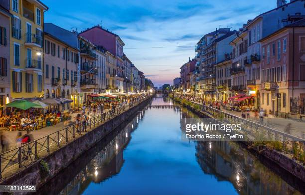 canal amidst illuminated city buildings against sky - milan stock pictures, royalty-free photos & images