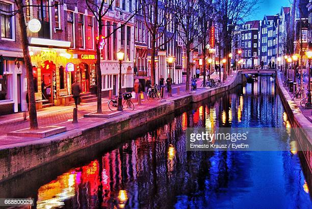 canal amidst illuminated street lamps against buildings in city - krausz stock-fotos und bilder