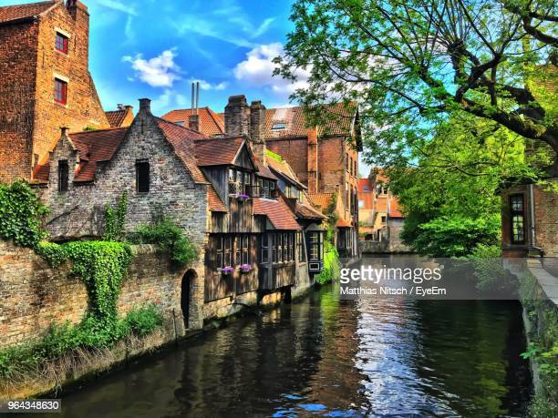canal amidst old buildings against sky - belgium stock pictures, royalty-free photos & images