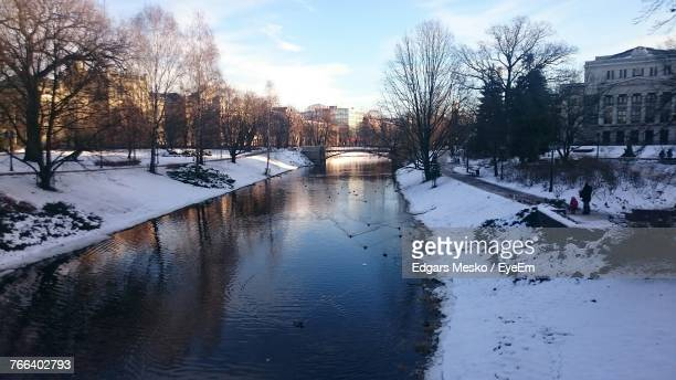 Canal Amidst Snow Covered Land Against Sky In City