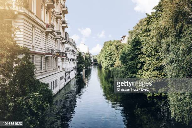 canal amidst trees and buildings against sky - hamburg germany stock pictures, royalty-free photos & images