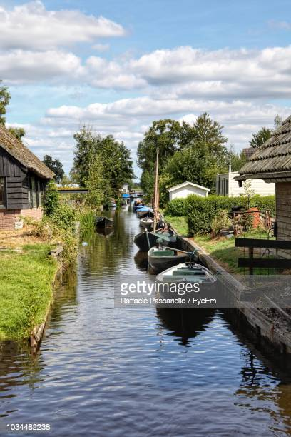 canal amidst trees and buildings against sky - giethoorn stock pictures, royalty-free photos & images