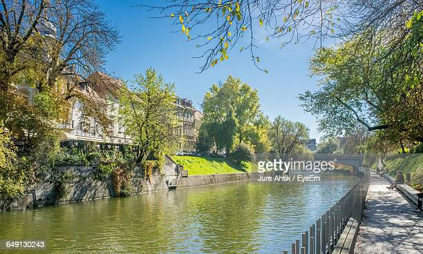Canal Amidst Trees And Buildings On Sunny Day