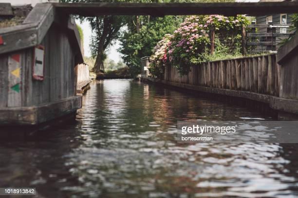 canal amidst trees and buildings - bortes fotografías e imágenes de stock