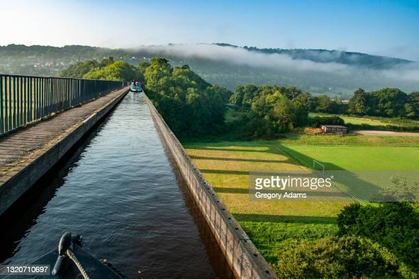 canal barging over an aqueduct on the llangollen canal in the united kingdom - canal stock pictures, royalty-free photos & images
