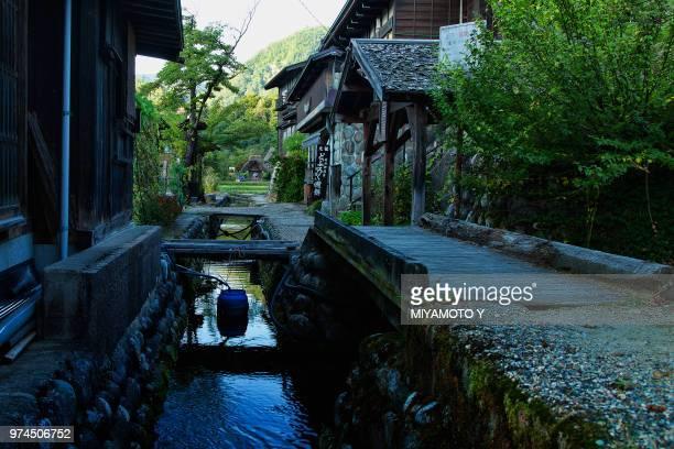 canal between buildings, shirakawa-go, japan - miyamoto y ストックフォトと画像