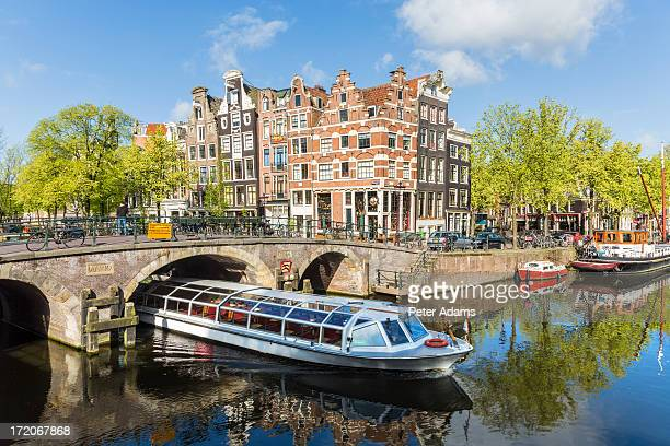 canal & boat, amsterdam, holland, netherlands - tourboat stock pictures, royalty-free photos & images