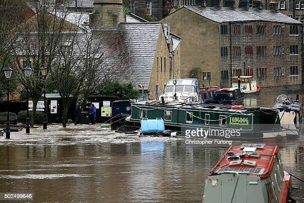 A canal boat collides with a rubbish bin as floodwaters rise after rivers burst their banks on December 26 2015 in Hebden Bridge England There are...