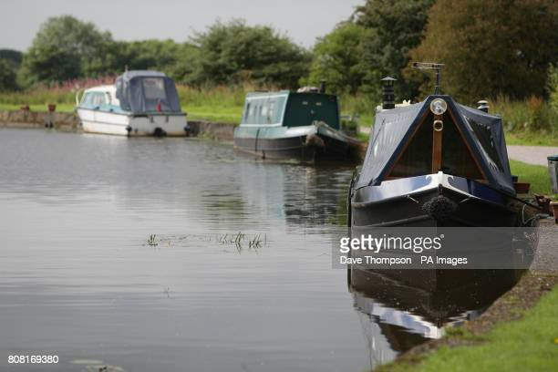 Canal boats moored up on a stretch of the Leeds Liverpool canal in Wigan