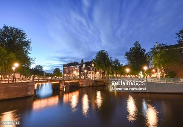 Canal bridges illuminated at dusk with reflection on canal waters, Amsterdam