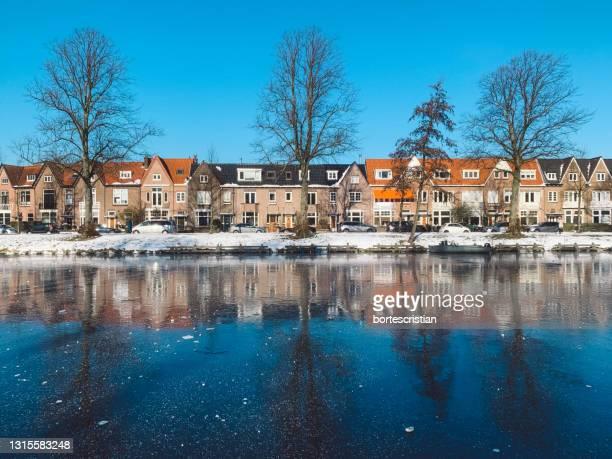 canal by buildings against blue sky - bortes fotografías e imágenes de stock