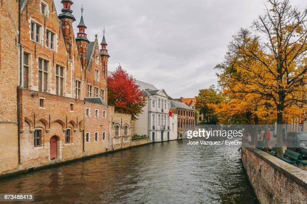 canal by buildings against sky during autumn - ブルージュ ストックフォトと画像