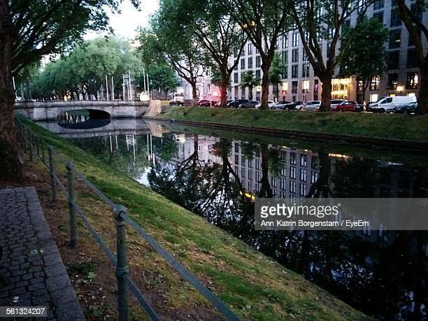Canal By Buildings And Trees At Dusk