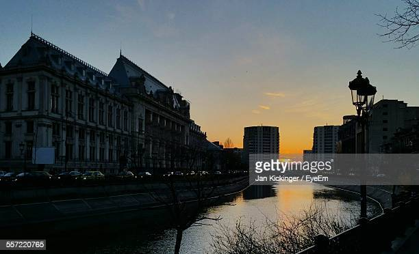 Canal By Buildings In City Against Sky At Sunset