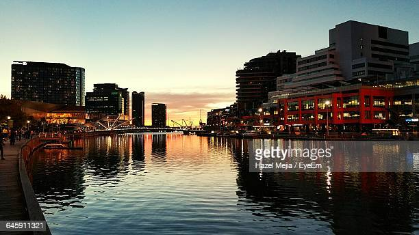 Canal By Illuminated Buildings In City Against Sky During Sunset