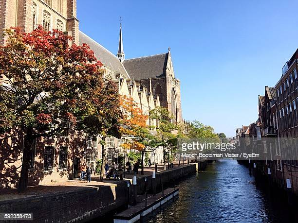 canal by street amidst buildings - dordrecht stock pictures, royalty-free photos & images