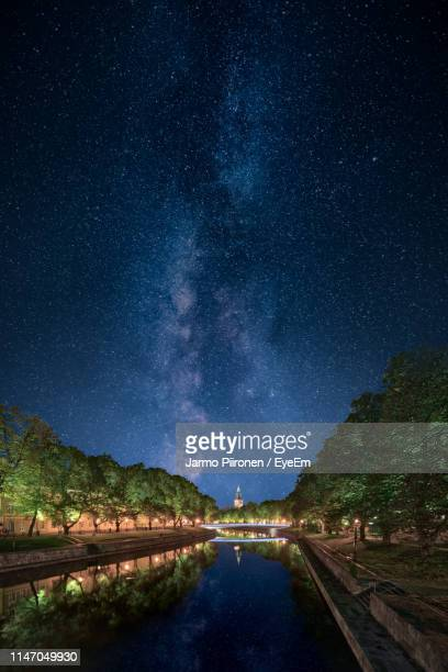 canal by trees against sky at night - トゥルク ストックフォトと画像