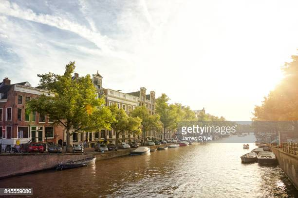 canal in amsterdam at sunset, netherlands - amsterdam stock pictures, royalty-free photos & images