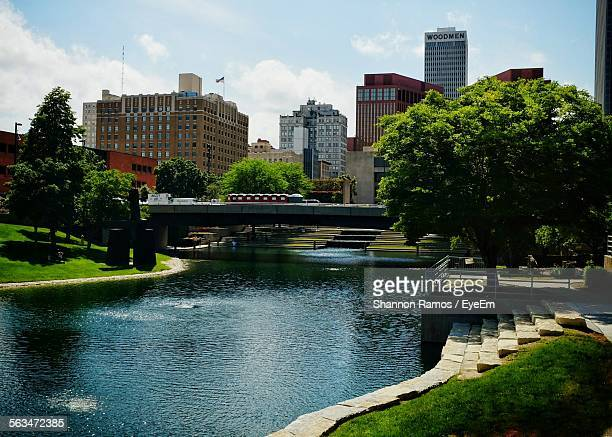 canal in front of cityscape against sky in city - nebraska stock photos and pictures