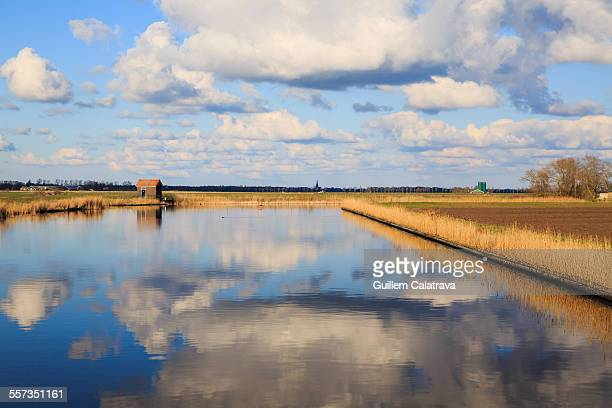 A canal in Holland with sky reflected at the water