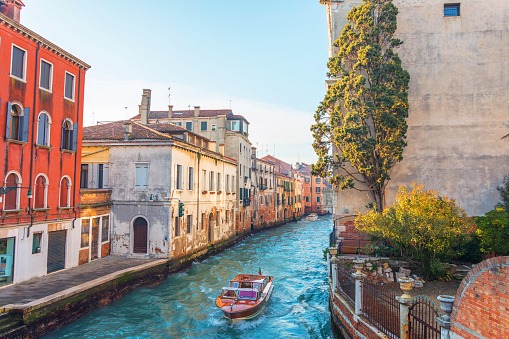Canal in Venice with a small garden and a tree near the house, on the water a small motor boat. 1126771319