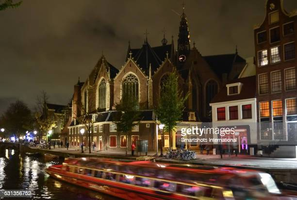 Canal, old church 'Oude Kerk' and Red Light District illuminated at night in Amsterdam, Netherlands